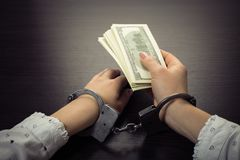 Hands in handcuffs holding paper money. On a wooden background stock photos