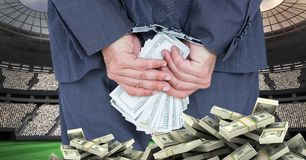 Hands with handcuffs and money at football stadium representing corruption Stock Image