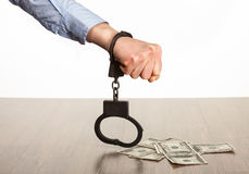 Hands in handcuffs and money  on the table Stock Image