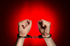 Hands with handcuffs on red background Stock Image