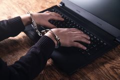 Hands in handcuffs typing on keyboard. Cyber Crime Concept stock image