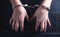 Hands in handcuffs typing on keyboard. Cyber Crime Concept stock photos