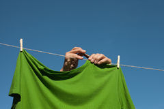 Hands hanging clothes. Royalty Free Stock Image