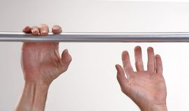 Hands hanging a metallic bar. Royalty Free Stock Image