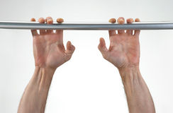 Hands hanging a metallic bar. Royalty Free Stock Images
