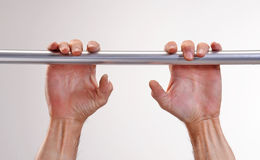Hands hanging a metallic bar. Stock Photo