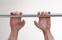 Hands hanging a metallic bar. Stock Image
