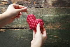 Hands hanging red heart. Female hands hanging red heart on rope on wooden background stock photos