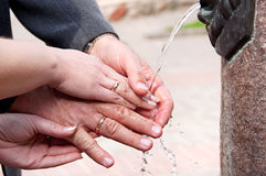 The hands of a happy elderly couple. Happy elderly couple washes his hands in the fountain Royalty Free Stock Images