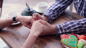 Hands of Happy loving couple. Gently caress, rub. Cookies and tea on the table. stock footage