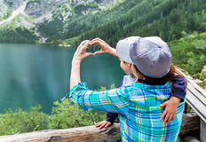 Hands of happy mother make a heart sign for her son near like. Royalty Free Stock Images