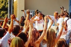 Hands of happy people crowd having fun at stage at holi fest, fe. Stival of colors in summer stock photos