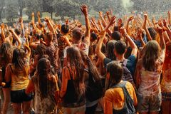 Hands and happy people crowd partying under rain at holi fest, f. Estival of colors in summer, amazing moment stock photo