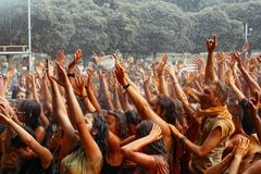 Hands and happy people crowd partying under rain at holi fest, f. Estival of colors in summer, amazing moment stock image