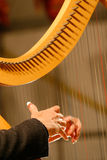 Hands on harp. A woman playing harp during a concert Royalty Free Stock Photography