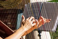 Hands on harp strings. Female hands on harp strings royalty free stock photo