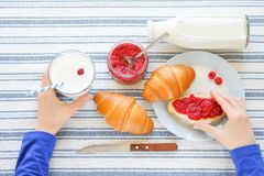 In the hands of have girls the glass with milk and sandwich with jam. There are croissants, jam, a bottle of milk, a knife on a royalty free stock photos