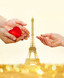 Hands and hear. Artificial red heart on hands of man for woman on Eiffel Tower background Royalty Free Stock Photography