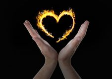 Hands with heart fire icon over. Black background Royalty Free Stock Photos