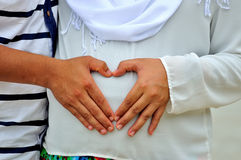 Hands in a heart shape on baby bump Royalty Free Stock Images