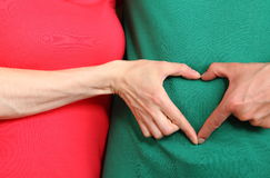 Hands in heart shape on belly, symbol of love Stock Images