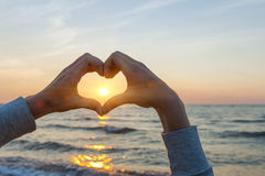 Hands in heart shape framing sun. Hands and fingers in heart shape framing setting sun at sunset over ocean Royalty Free Stock Photos