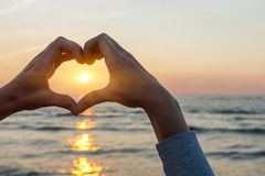 Hands in heart shape framing sun. Hands and fingers in heart shape framing setting sun at sunset over ocean Stock Photos