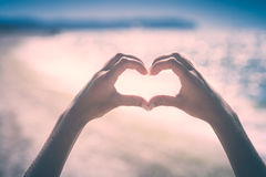 Hands in heart shape. Instagram stylisation. Young wooman`s hands in heart shape showing love friendship on blurred sea background. Instagram stylisation Stock Photos