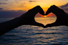Hands in heart shape at sunset on beach.  Royalty Free Stock Photos