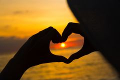 Hands in heart shape at sunset on beach.  Stock Photos