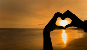 Hands with a heart shape at sunset on a beach. Spain Stock Images