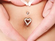 Hands heart symbol around navel piercing Royalty Free Stock Photo