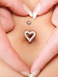 Hands heart symbol around navel piercing Royalty Free Stock Photography