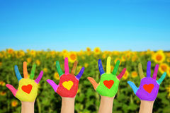 Hands with hearts, eco friendly concept. Helping hands with hearts on the palms against nature background. The eco friendly concept Royalty Free Stock Photos