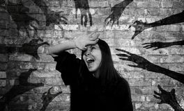 Hands from hell. Young woman is screaming with terror surrounded by shadows of hands reaching for her Stock Photos
