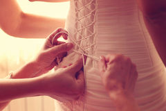Hands helping the bride with her wedding dress Stock Image
