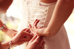 Hands helping the bride with wedding dress Stock Photos