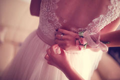 Hands helping the bride with wedding dress Royalty Free Stock Photos