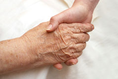 The hands of her grandmother and granddaughter. On a light background Stock Photos