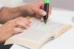 Hands highlighting text in book on the table. Closeup of a mans hands highlighting text in book on the table Stock Image