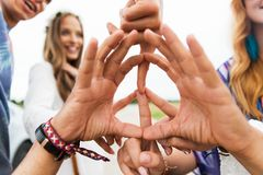 Hands of hippie friends showing peace sign. Youth culture, gesture and people concept - close up of hippie friends showing peace hand sign outdoors royalty free stock photos