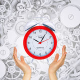 Hands hold alarm clock with gears Stock Image