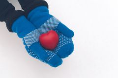 Hands hold antistress toy heart. Hands in woolen mittens. valentines day card concept. Woman in woolen mittens hold red antistress toy heart in winter forest Royalty Free Stock Photography