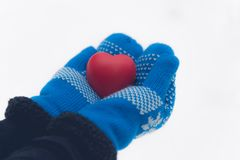 Hands hold antistress toy heart. Hands in woolen mittens. valentines day card concept. Woman in woolen mittens hold red antistress toy heart in winter forest Stock Photography