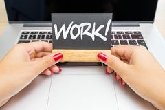 Hands hold backboard with work lettering with laptop in background stock image