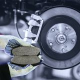Hands hold brake pads with shallow depth of field. Gloved hands hold brake pads with shallow depth of field royalty free stock photography