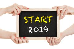 Hands hold chalkboard for the new year 2019 - isolated on white background.  royalty free stock photo