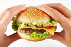Hands hold a cheeseburger Royalty Free Stock Photography