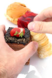 Hands that hold the chocolate cake. Cose-up of a hand that reaches down to the cakes Royalty Free Stock Photo