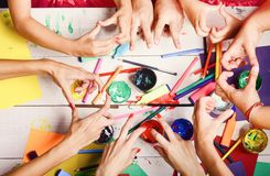 Hands hold colorful markers, pencils and paints. Art and craft concept. Artists hands with stationery and paper. Art supplies and hands showing victory and stock photo